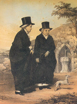 Two ladies wearing long black coats and black top hats