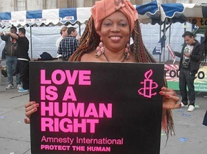 "Ilesanmi holding a banner saying ""Love is a Human Right"""
